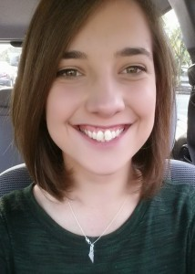 A selfie in a car - Sasha smiles while wearing a green shirt.