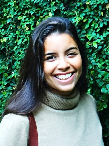 Claudia smiles in front of some beautiful greenery wearing a tan turtleneck.