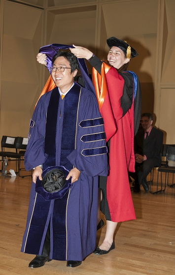 Dr. Kat Steele recognizes Hwan Choi by performing the hooding ceremony.