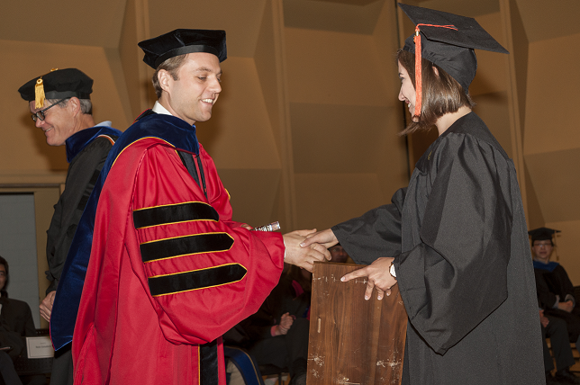 Nate Sniadecki shakes hands with Sasha Portnova as he hands her the Undergraduate Research award placard at the graduation ceremony.