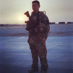 Michael Wang stands in his military uniform at sunset.