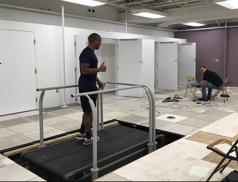 Darrin stands on the left belt of the new treadmill within the AMPLab's space, while Dave the Bertec Technician tests the isntallation.