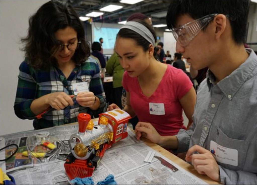 A team of volunteer students work together to solder an adaptive switch onto a toy in time for the holidays.