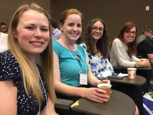 Brianna, Alyssa, Claire, and Heather sit in the auditorium seating during a brief break in podium presentations during the Northwest Biomechanics Symposium in Bellingham, WA
