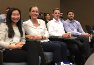 Madelyn, Karley, Leif, and Ben smile while they sit in the auditorium seating during a brief break in podium presentations during the Northwest Biomechanics Symposium in Bellingham, WA