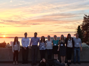 Leif, Madelyn, Ben, Claire, Karley, Alyssa, Brianna, Heather, Michael, and Keshia all pose in front of a Bellingham Bay sunset after dinner and trivia during the Northwest Biomechanics Symposium at Western Washington University.