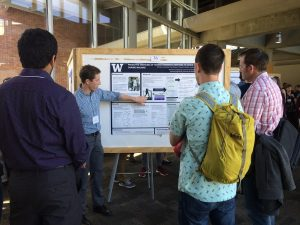 Michael Rosenberg, wearing a blue dress shirt and slacks, points towards a method figure on his poster while sharing about his research at the Northwest Biomechanics Symposium. Three community members look on and learn from Michael and his research poster.