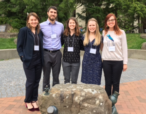 Nataliya, Ben, Keshia, Brianna, and Heather all pose arm in arm near a Western Washington University campus sculpture during the walk to the Symposium dinner.
