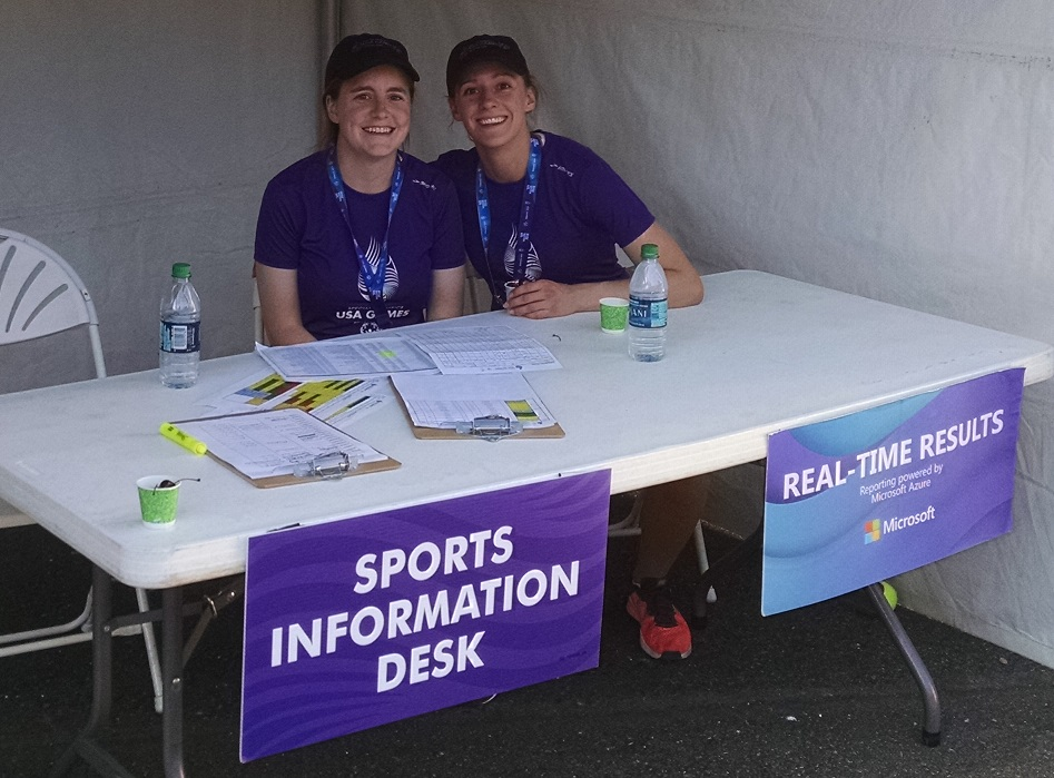 "Alyssa Spomer and Karley Benoff sit behind a fold out table underneath a white tent as they provide answers for athletes and families alike. The desk has two purple informational signs that read, ""Sports Information Desk"" and ""Real-Time Results"""