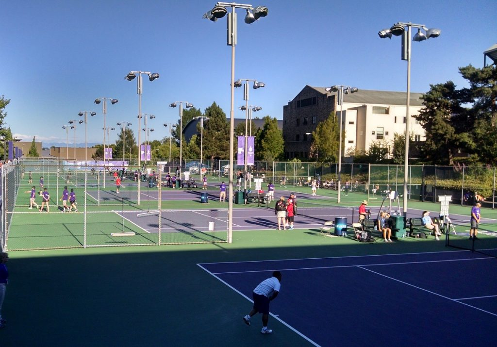 Purple and green tennis courts at UW span the photo. In the foreground an athlete finishes his/her serve as referees and volunteers look on.