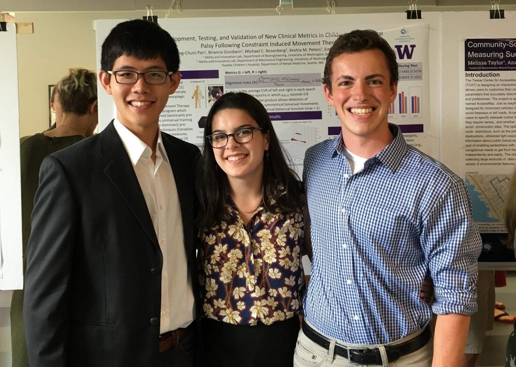 Three undergraduates, in their early twenties, stand arm in arm as they smile for the photo. They are dressed in business casual attire and behind them hangs a series of scientific posters on biomechanics.