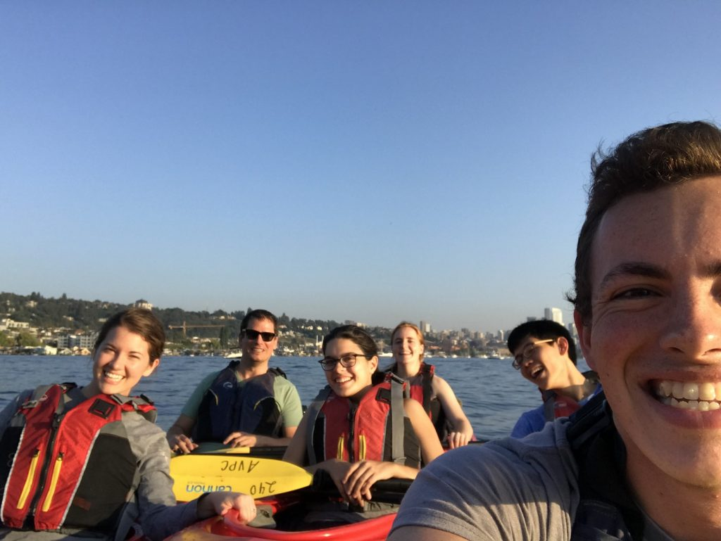 Six smiling researchers squeeze into a selfie-style photo while staying afloat in three two-person kayaks in Lake Union near Gas Works Park.