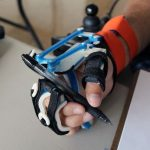 User wearing wrist driven orthosis and holding pen