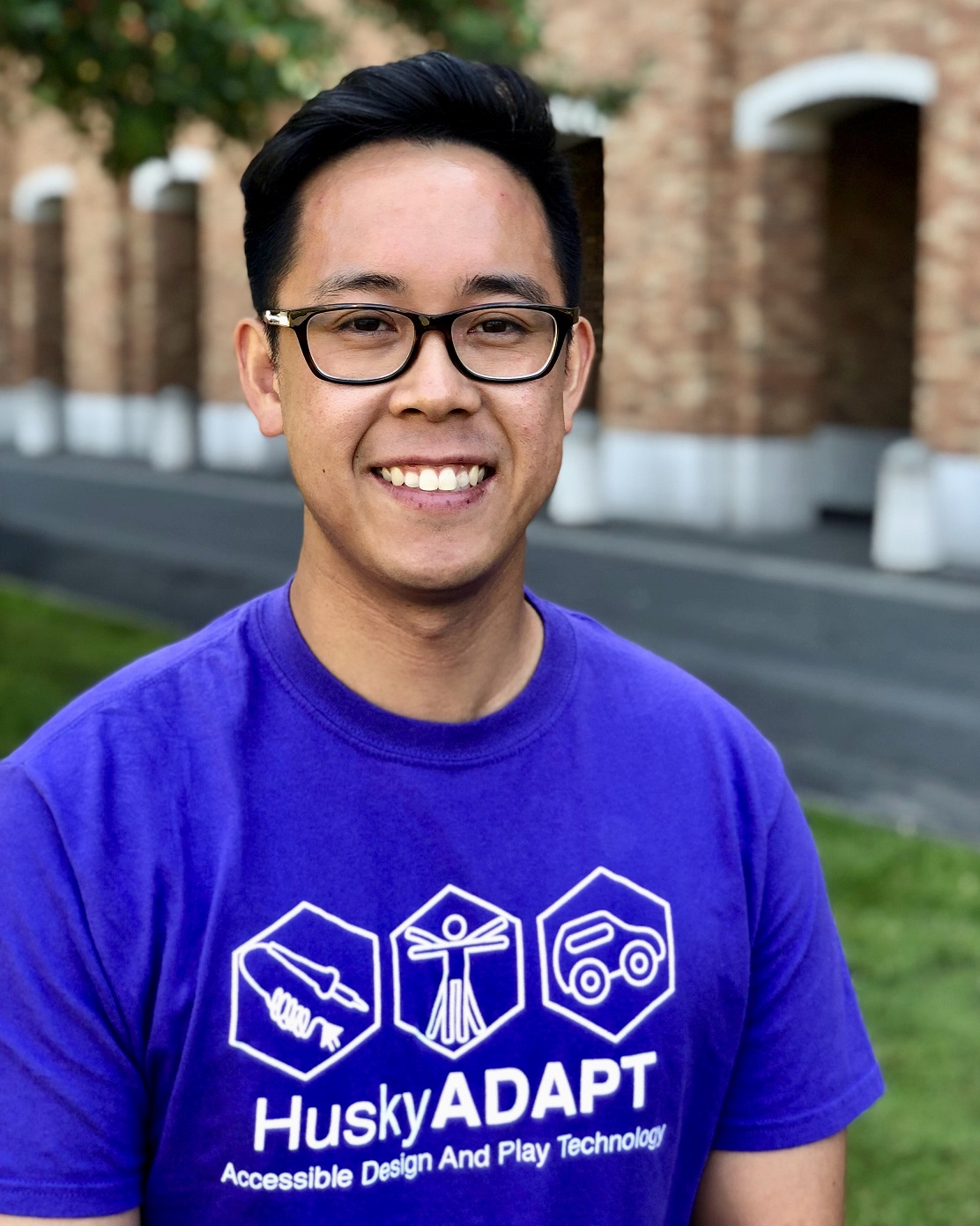 Brandon smiles at camera on the University of Washington campus in a bright purple HuskyADAPT t-shirt.