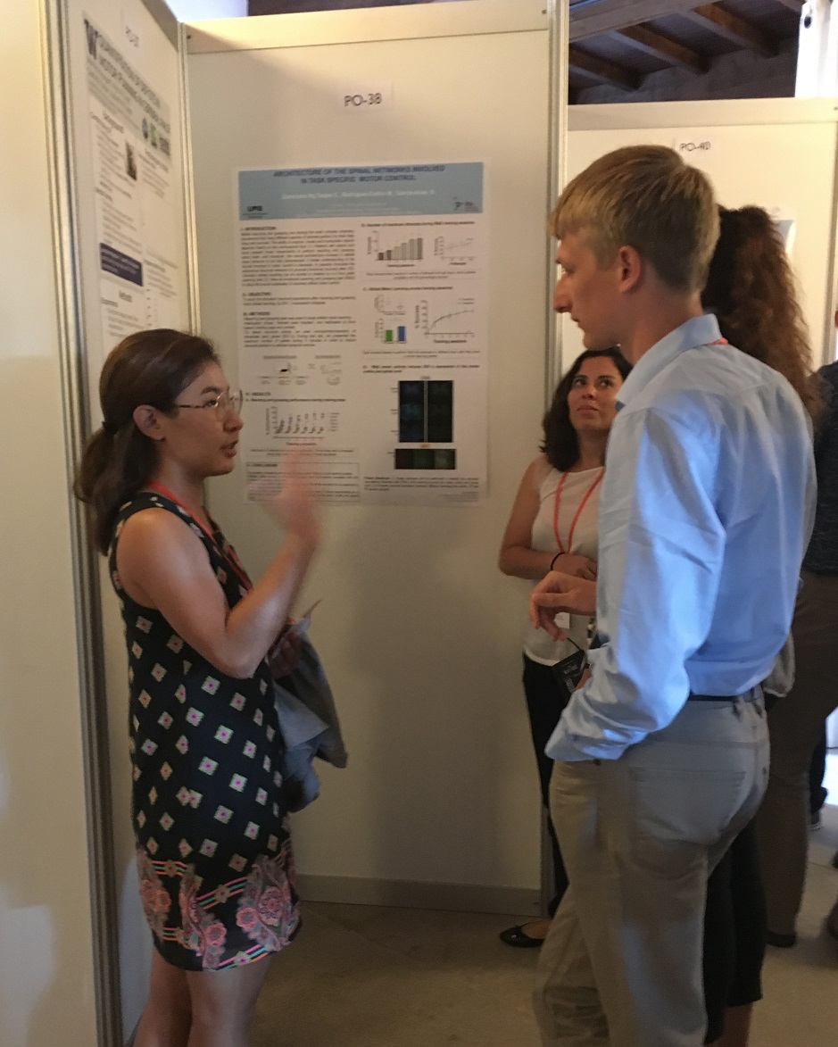 "Monoma stands in front of her poster ""Quantification of Deficits in Motor Planning in Cerebral Palsy"", discussing with interested colleagues."