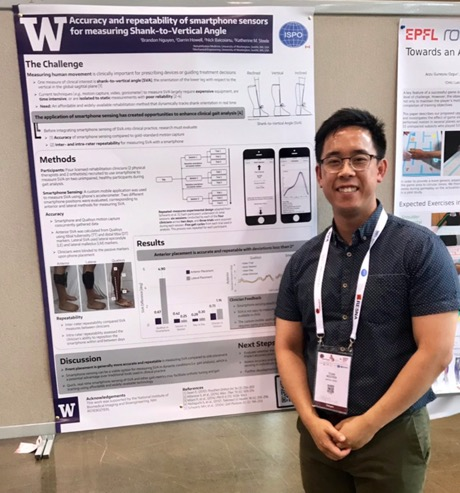 Brandon Nguyen standing in front of his poster at RehabWeek wearing a dark blue shirt. His poster features images of the smartphone app and graphs.