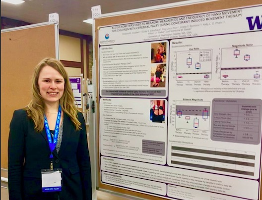 Brianna Goodwing stands in front of her poster in a black jacket at the conference.