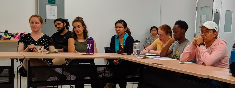 Students listen attentively to the Q&A Panel. Some look bored, some look amused, and one is even taking notes, or maybe doodling!