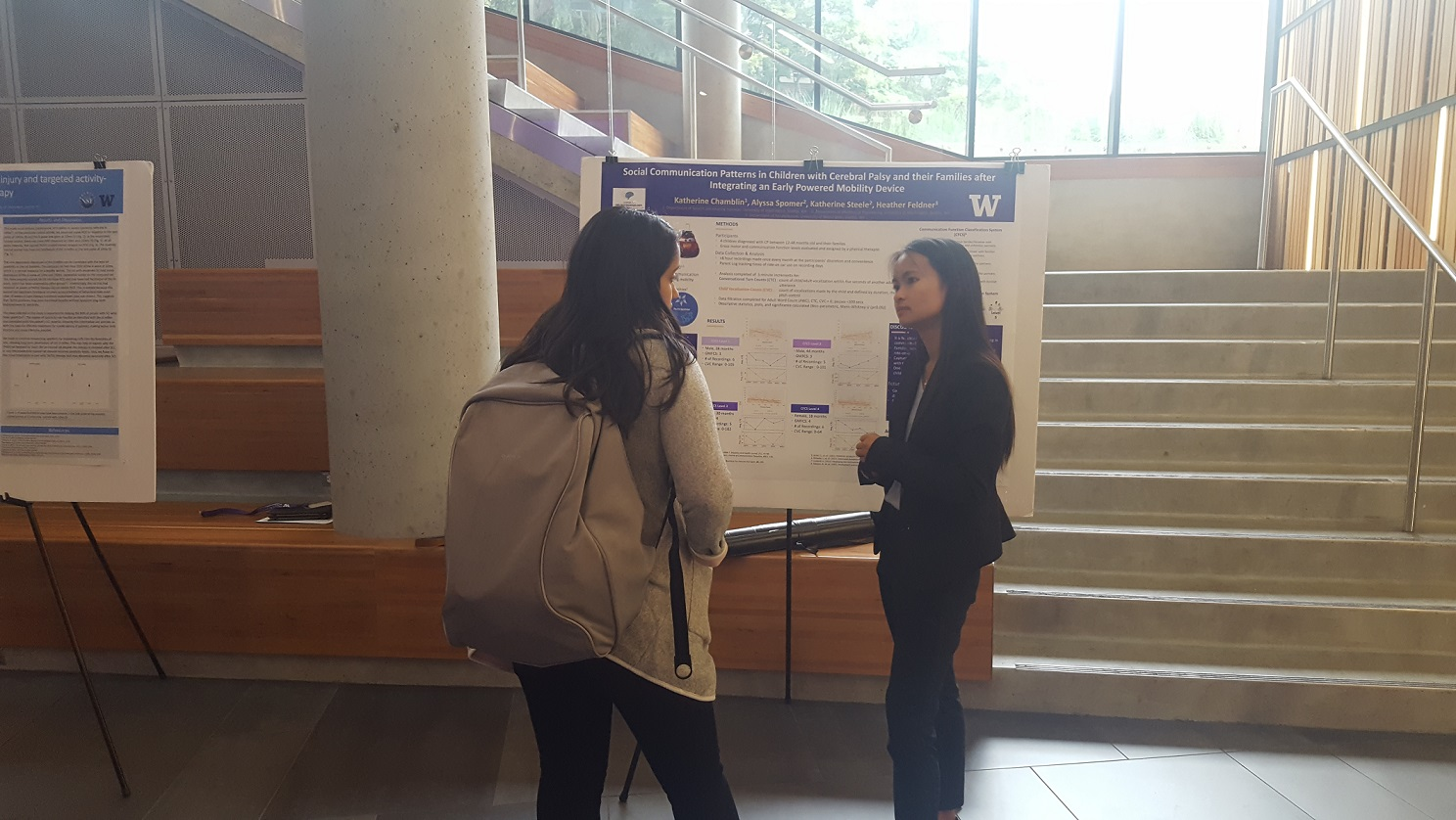 Sun shinning down on young woman in business attire talking to another woman in front of a white and purple poster board