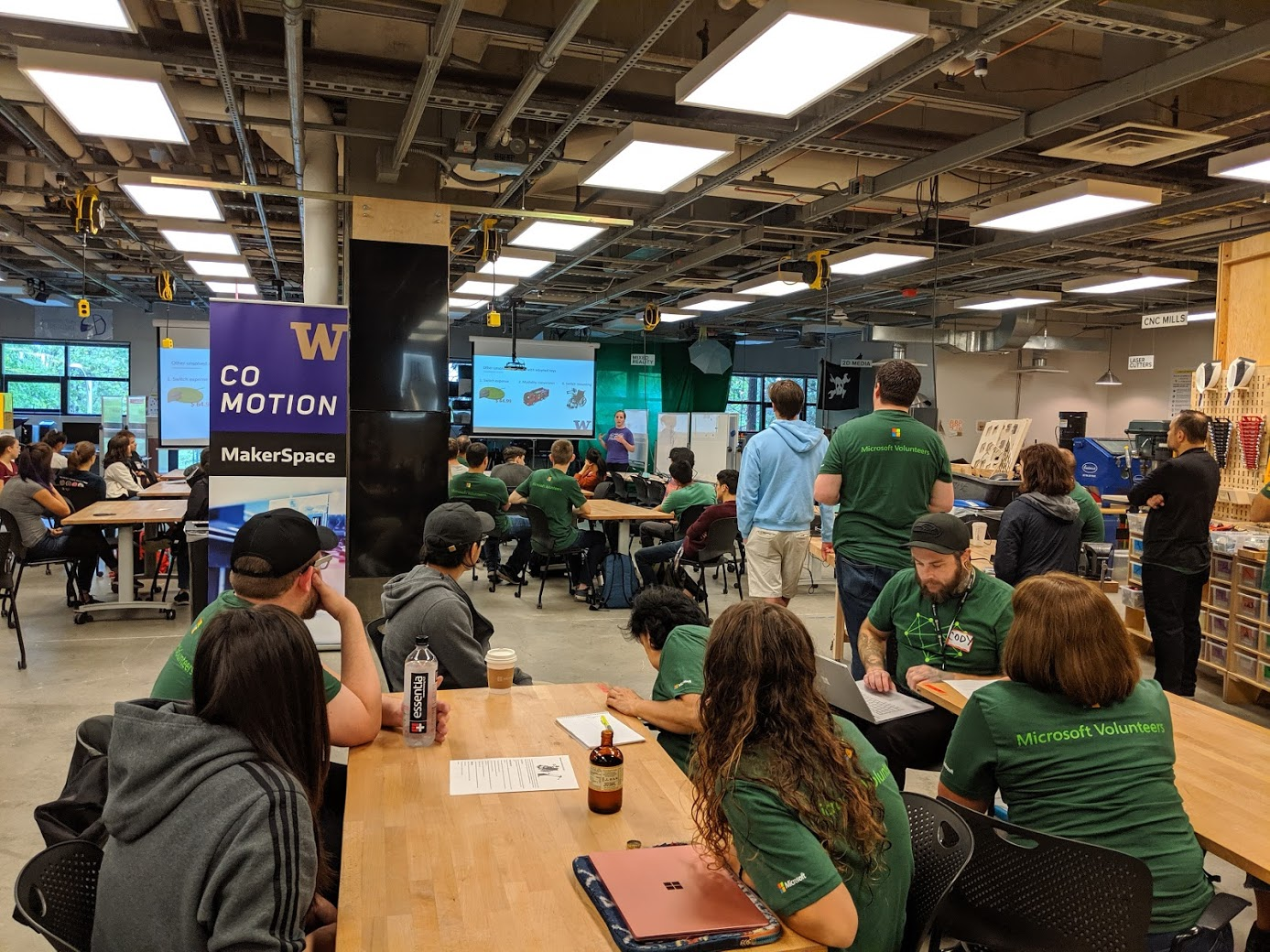 Younger woman in purple giving a presentation on two projection screens in a design space while a many others wearing green shirts look on