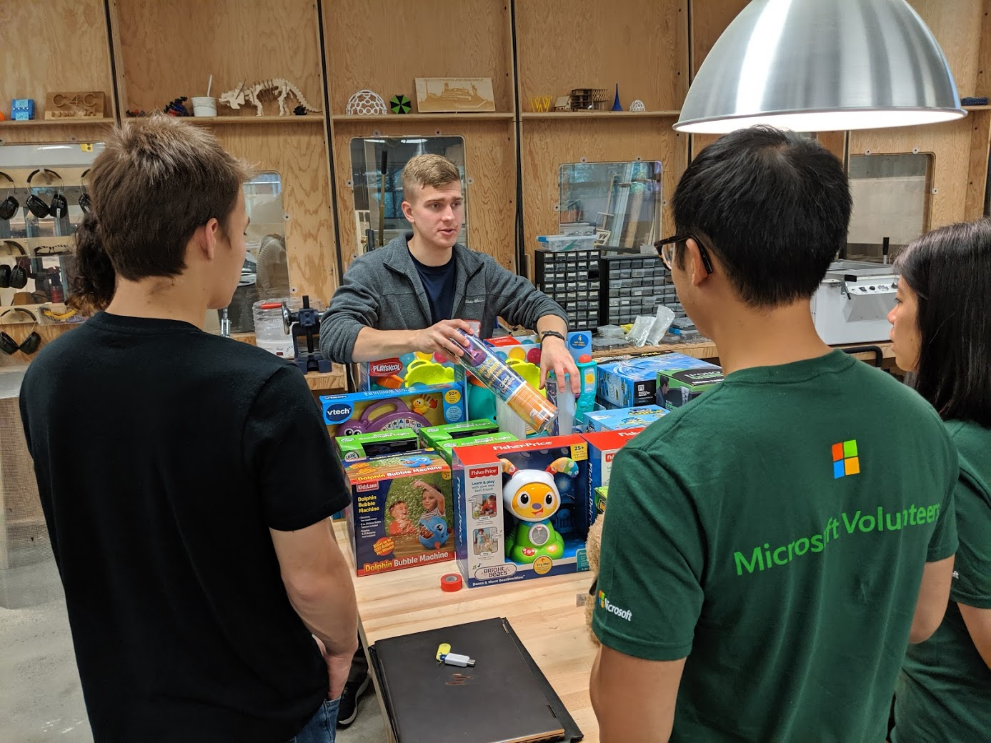 Several people, two in green shirts and one in a black shirt, listen to a young gentleman in a gray jacket as he talks about the toys in front of him