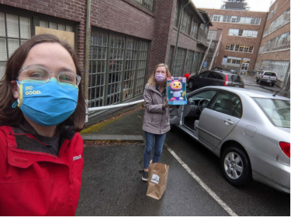 Foregroud: woman wearing clear glasses smiling behind mask. Background: woman holding toy smiling behind mask next to car